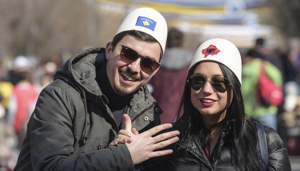 Egy pár tardicionális albán sapkában, melyeken Albánia és Koszovó zászlaja látható, egy ünnepségen Koszovóban 2018. április 17-én Fotó:EUROPRESS/AFP/Armand Nimani #moszkvater