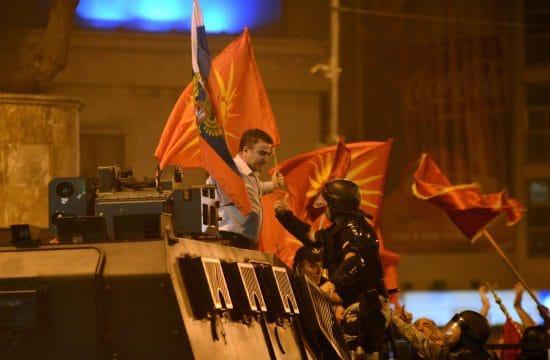 Egy tüntető orosz és macedón zászlóval a kezében egy rendőrrel szemben 2018. június 17-én Szkopjéban azután, hogy Macedónia megegyezett nevének megváltoztatásáról Görögországgal #moszkvater