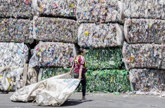 Egy munkás bálázott műanyagpalackok előtt egy zsákot húz maga mögött egy Costa ricai szeméttelepen #moszkvater