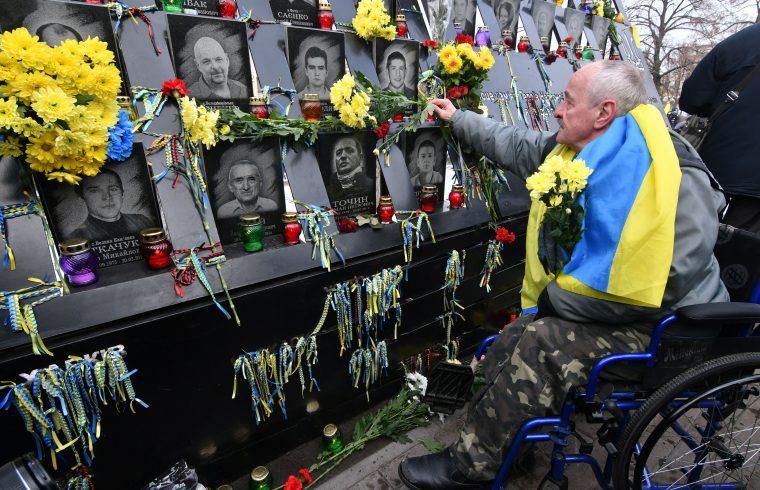 Egy kerekesszékes férfi virágokat helyez a meggyilkolt Maidan-aktivisták emlékére az Euromaidan ötödik évfordulója alkalmából rendezett ünnepségen, 2018. november 21-én Kijev központjában #moszkvater