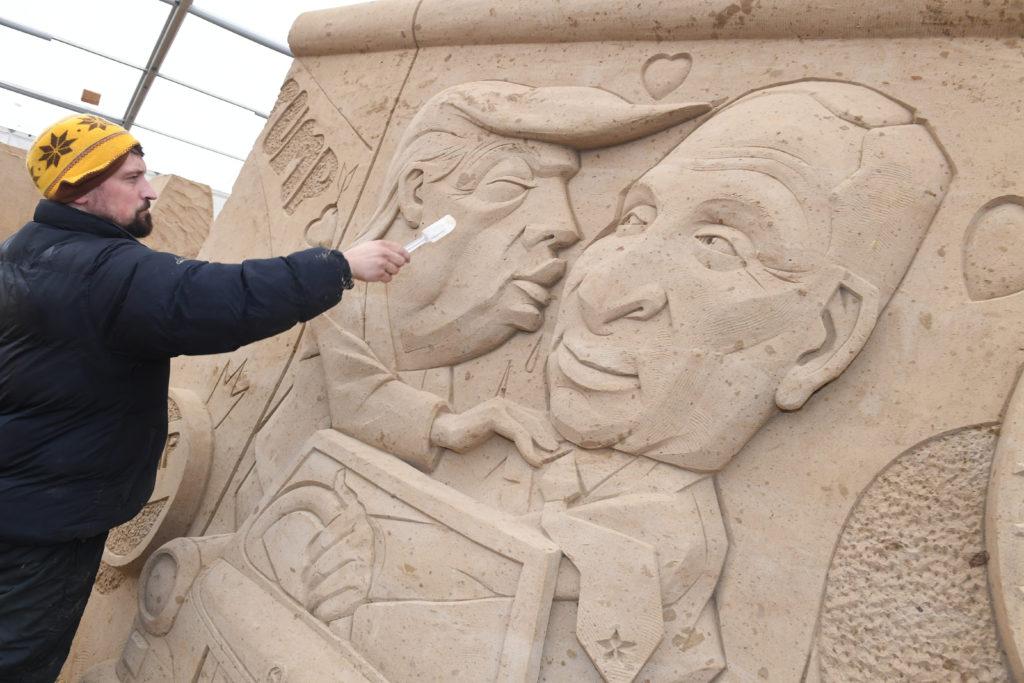 """Wodek Bludik lengyel szobrászművész homokszobrén dolgozik a berlini Eastside Galéria által kiírt """"Testvéri csók"""" pályázatra készülő alkotásával a Balti-tenger partján fekvő Binz városában rendezett homokszobor fesztiválon 2019. február 12-én Fotó:EUROPRESS/AFP/DPA/Stefan Sauer #moszkvater"""