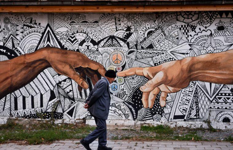 Idős ember sétál el a koszovói Ferizaj településen egy ház falára festett graffiti előtt 2019. november 3-án #moszkvater