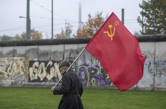 Szovjet zászlóval és katonai egyenruhában sétál egy férfi a Berlini fal előtt 2019. november 9-én Berlinben, a fal leomlásnak harmincadik évfordulójának ünnepe előtt #moszkvater