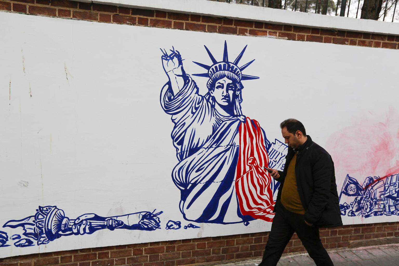 Egy iráni járókelő nézi a mobilját a teheráni USA nagykövetség falára rajzolt graffitti előtt sétálva 2020. január 4-én #moszkvater