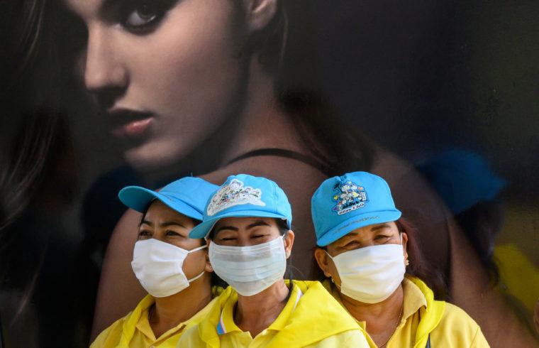 Védőmaszkot viselő önkéntesek fertőtlenítenek egy gyalogoshidat Bangkokban, a koronavírus elleni küzdelemben 2020. február 24-én #moszkvater