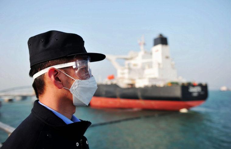 Egy maszkot viselő kínai rendőr figyeli Quangdong kikötőjében, ahogy egy kuvaiti tartályhajóról átfejtik az olajat #moszkvater