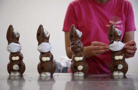 Maszkot viselő csokoládé nyulakat készítenek egy svájci kisüzemben 2020. március 27-én #moszkvater