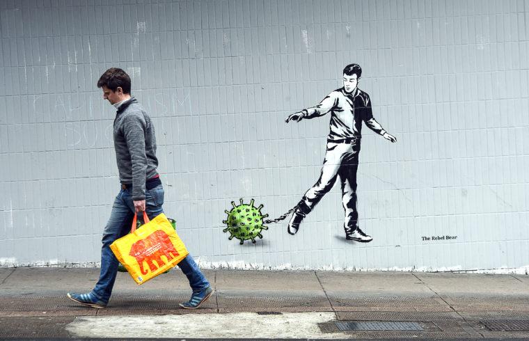Egy koronavírus ihlette graffiti előtt megy el egy férfi Glasgow-ban 2020. április 4-én #moszkvater