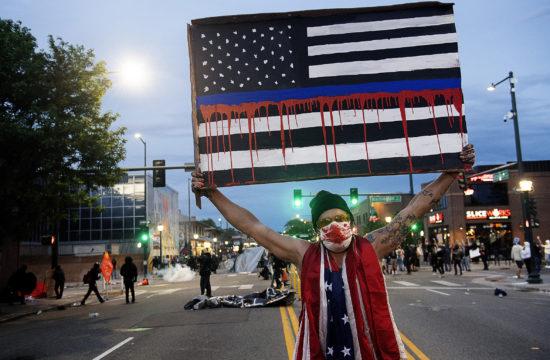 Egy tüntető tartja a magasba a vérző amerikai zászlót ábrázoló rajzot Denverben 2020. május 31-én #moszkvater
