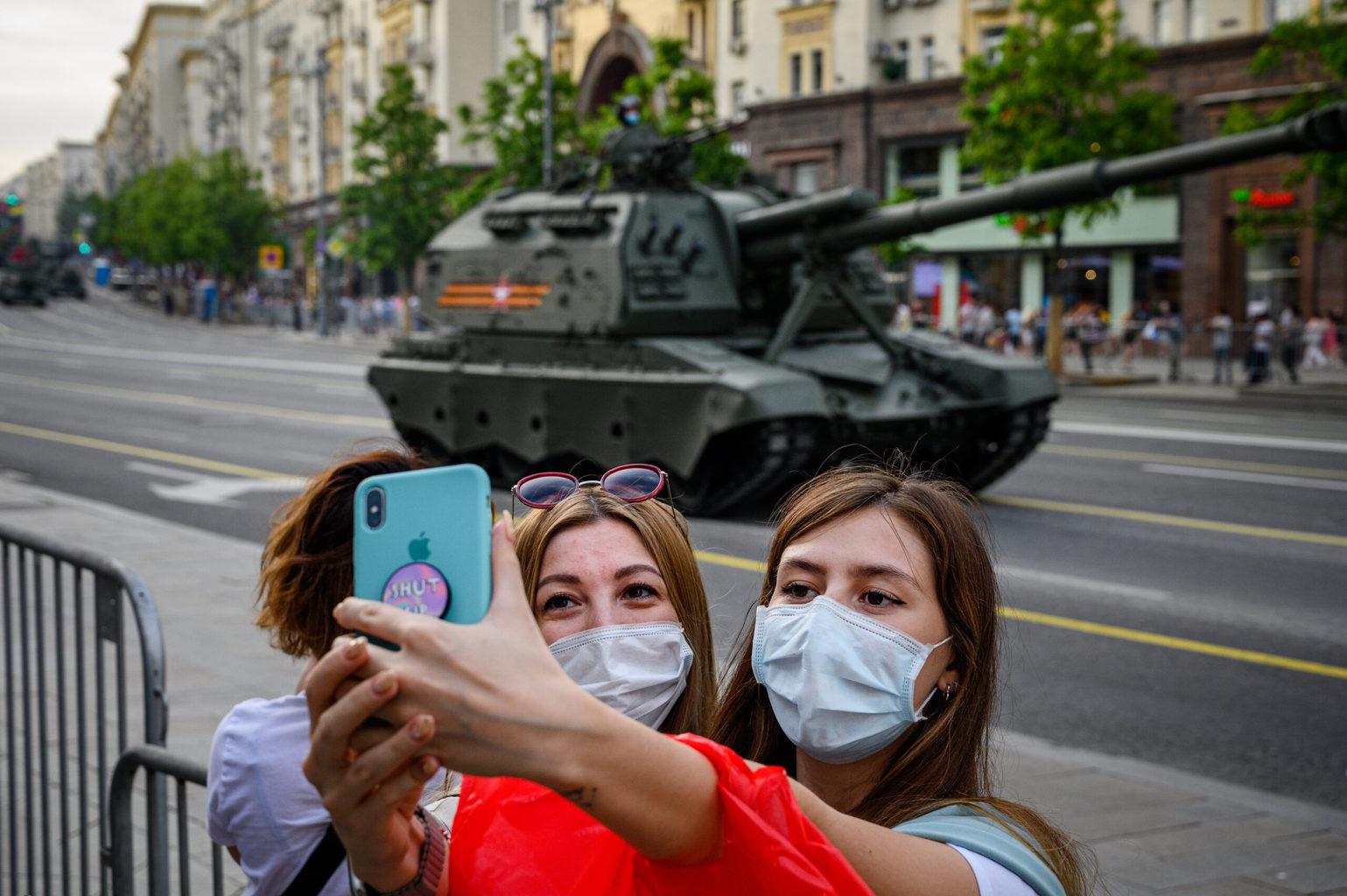 Védőmaszkos hölgyek készítenek szelfit a Győzelem napjára rendezett parádé próbáján egy harckocsi előtt Moszkvában 2020. június 17-én #moszkvater