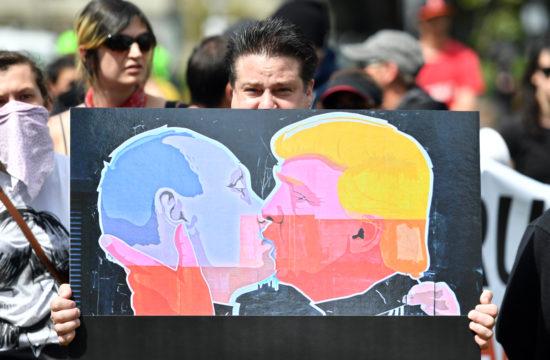 Egy tüntető Vlagyimir Putyint és Donald Trumpot ábrázoló plakátot tart a kezében egy Trump-ellenes tüntetésen 2017. április 15-én a kaliforniai Berkeley-ben #moszkvater