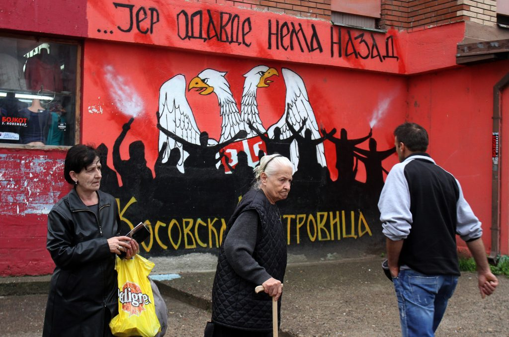 Koszovói szerbek sétálnak egy graffiti előtt Mitrovicában 2013. október 9-én Fotó:EUROPRESS/AFP/Sasa Djordjevic #moszkvater