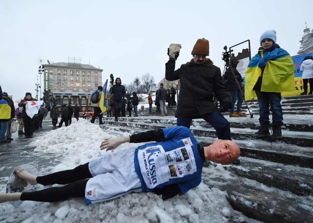 """Egy férfi kővel dobja meg a Putyin, orosz elnököt ábrázoló bábut Kijevben, a ,,Kick Out Putin"""" flashmobon 2018. január 22-én, amelyen bojkottra szólítanak fel a 2018-as oroszországi futball világbajnokságra"""