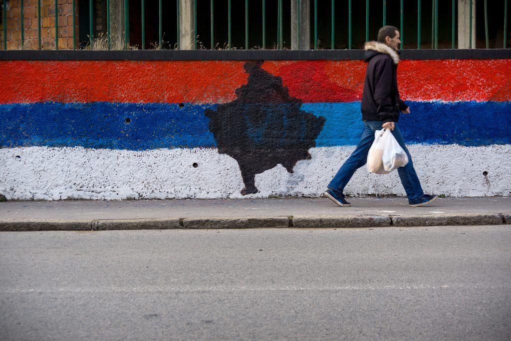 Egy férfi sétál el egy, a falra festett szerb lobogó előtt Belgrádban, amelynek a közepén Koszovó térképének a körvonalai vannak felfestve #moszkvater