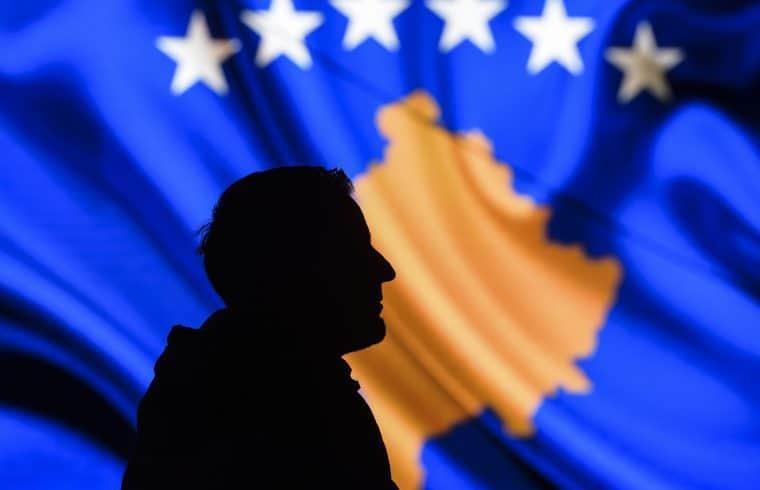 Egy férfi sziluettje egy kivetítő előtt, amely a koszovói zászló képét sugározza 2018. február 15-én Pristinában #moszkvater