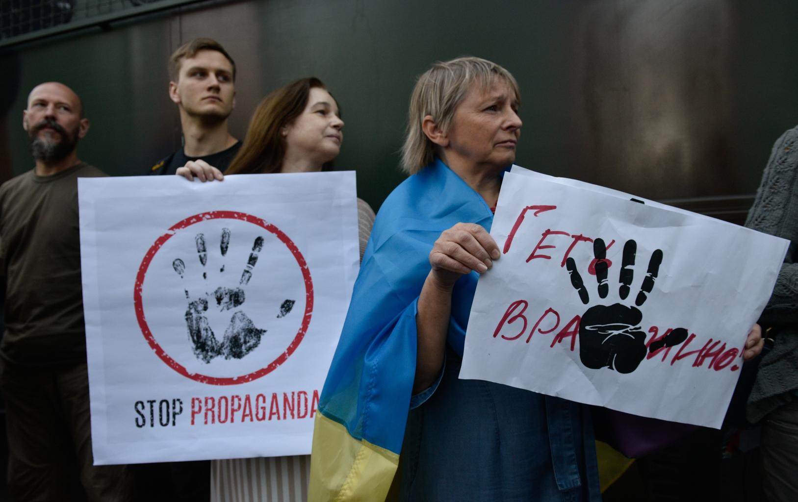 """""""Beszélnünk kell"""" feliratú táblát tart egy tüntető a Televíziós és Rádióműsorok Állami Bizottsága épülete előtt 2019. július 9-én Kijevben tartott demonstráción #moszkvater"""