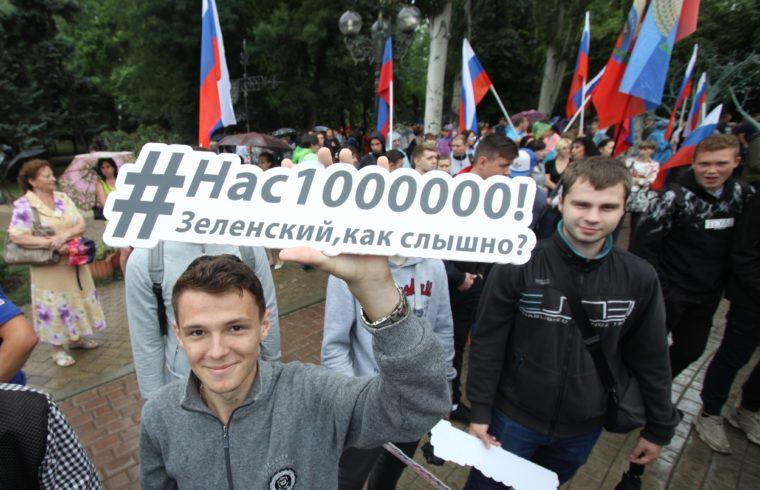 """""""Egymillióan vagyunk, Zelenszkij, hallasz?"""" feliratot tart egy táblán egy orosz tüntető Donyeckben 2019. július 6-án, tiltakozásul többek között az ukrán nyelvtörvény ellen #moszkvater"""