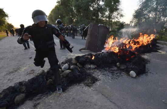 Egy rohamrendőr ugrik át egy égő kordont a kirgizisztáni Koj Tas faluban, ahol Atambajev kirgiz elnököt a lakóhelyén fegyveres összetűzéssel elfogták 2019. augusztus 8-án #moszkvater