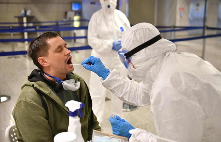 A moszkvai Seremetyevo repülőtéren egy érkező utast vizsgálnak az egészségügyi személyzet tagjai 2020. március 19-én #moszkvater