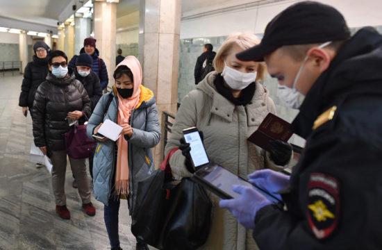 Egy rendőr ellenőrzi a kijárásra engedélyt adó digitális kódot egy utasnál a moszkvai Szokolnyiki metróállomáson 2020. április 15-én #moszkvater