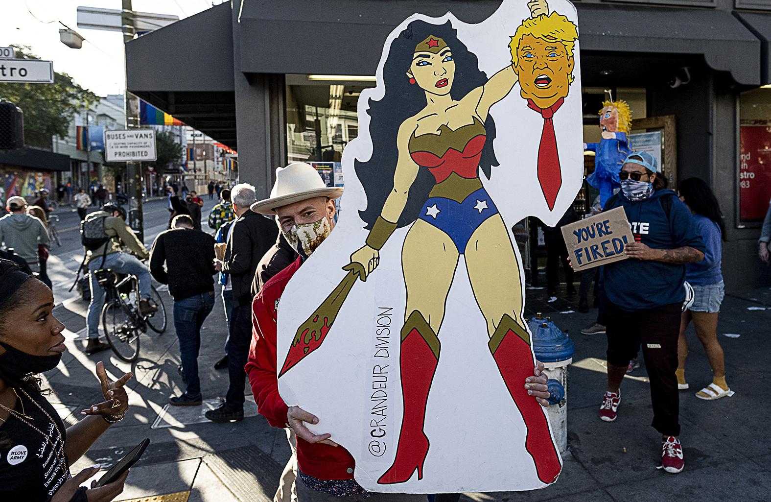 Mike Picot amerikai művész tartja plakátját, amelyen Wonder Woman fogja Donald Trump levágott fejét Joe Biden megválasztásának bejelentése után San Franciscoban egy utcai tüntetésen 2020. november 20-án #moszkvater