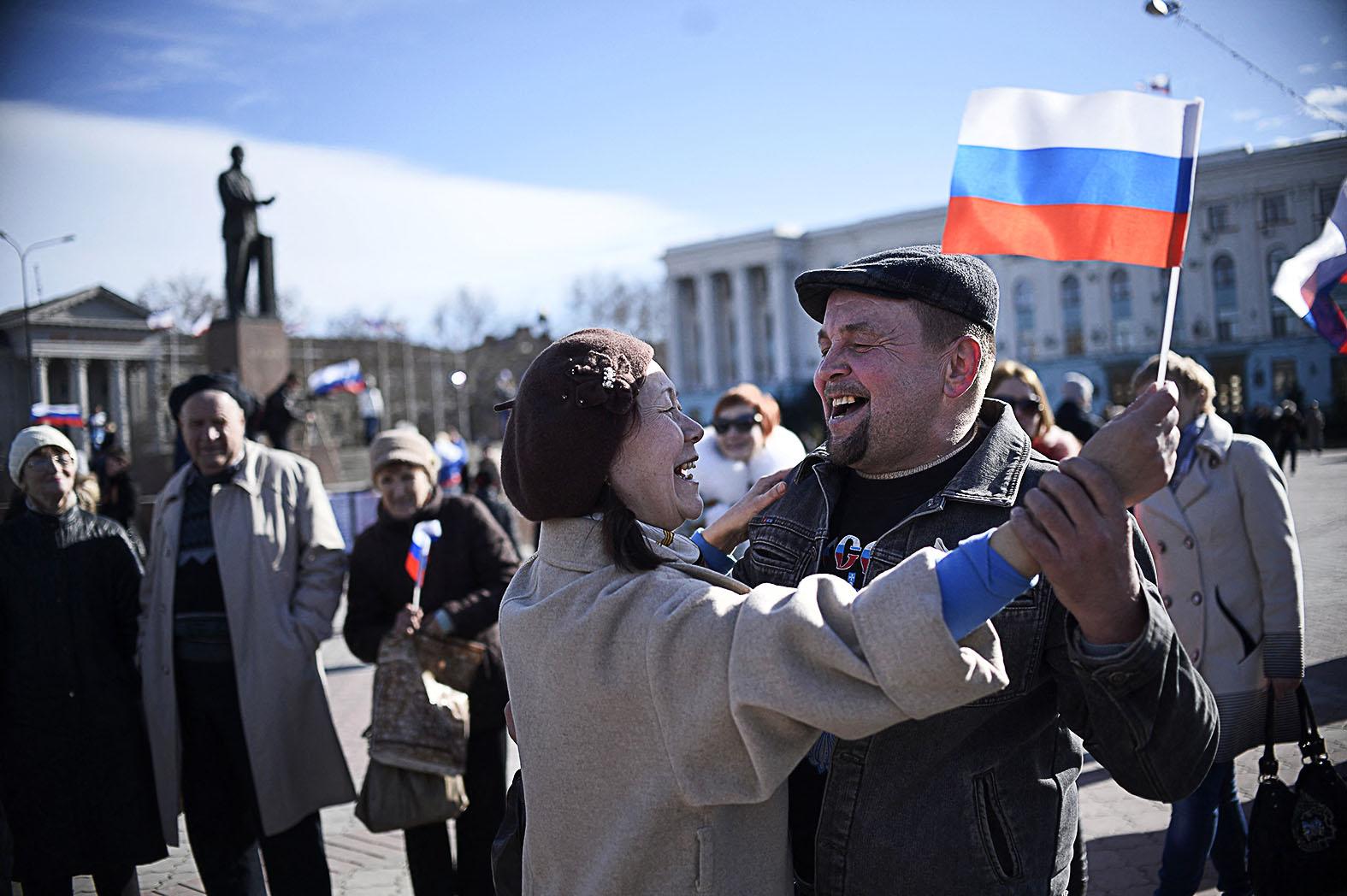 Orosz zászlóval a kezében táncol egy pár a Krím Oroszországhoz csatolásának napját ünnepelve Szimferopolban 2014. március 17-én #moszkvater