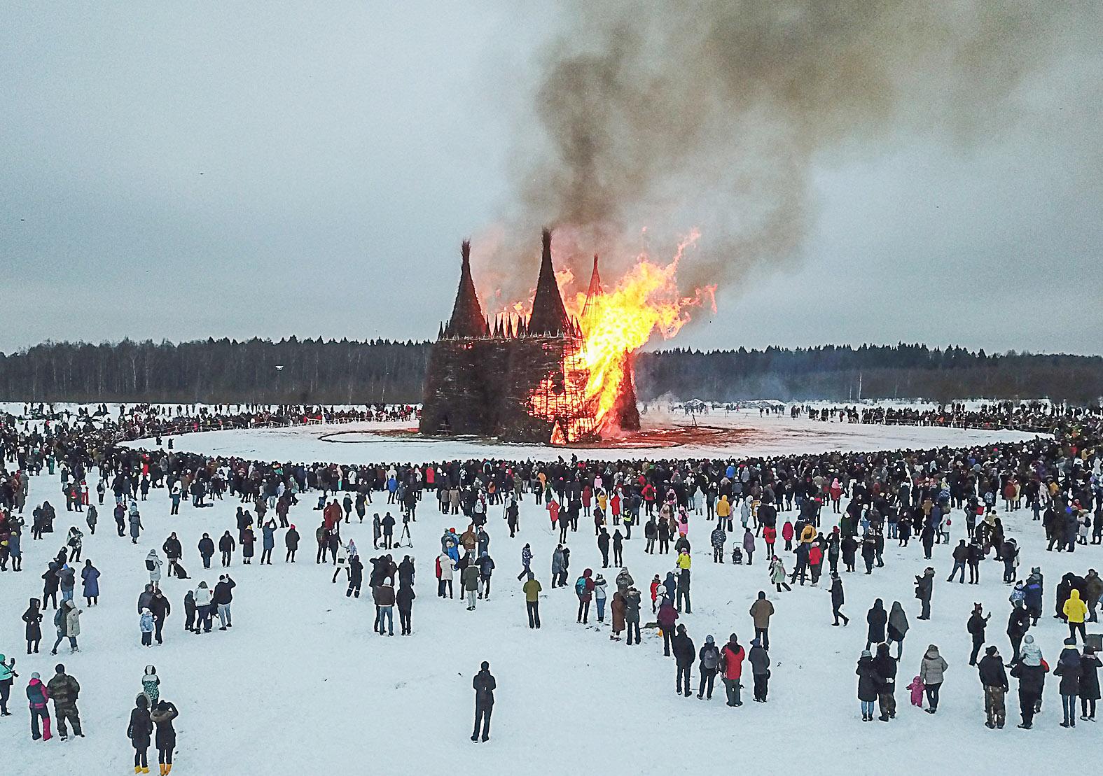 """Látogatók nézik a Kaluga tartományban található Nikola Lenivec faluban tartott a tél végét jelző pogány ünnepen, a Maszlenyica fesztiválon a felgyújtott """"oltás tornya"""" installáció lángolását 2021. március 13-án #moszkvater"""