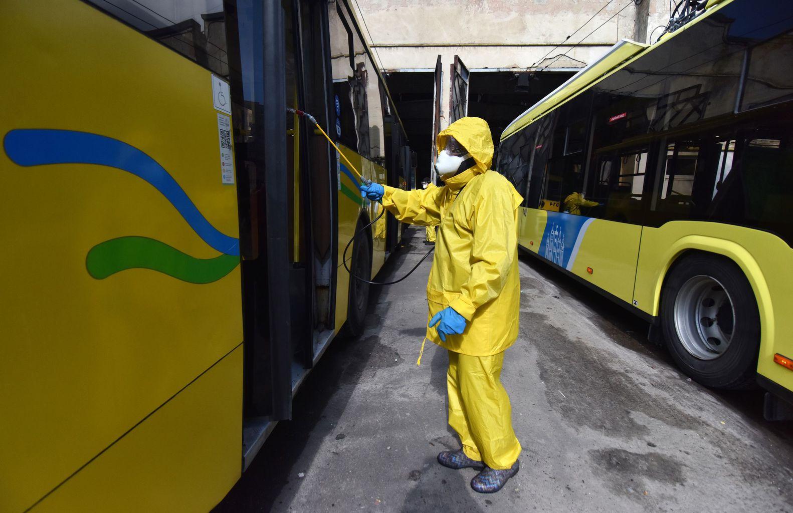 Biztonsági öltözetben fertőtleníti a buszokat egy munkás Lviv-ben, Ukrajnában 2020. március 12-én #moszkvater